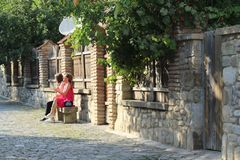 Die Mädchen sitzen auf Steinstuhl stockbild