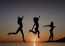 Die Mädchen springend in den Sonnenuntergang in Meer Stockbilder