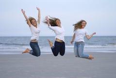 Die Mädchen springend für Freude auf Strand Lizenzfreies Stockfoto