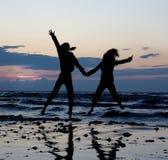Die Mädchen springend nahe Meer. Stockfotografie