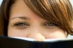 Die Mädchenblicke heraus wegen des Buchabschlusses oben Lizenzfreies Stockfoto