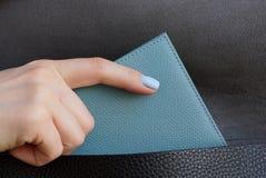 Die Mädchenhand nimmt einen grauen Geldbeutel von einer schwarzen Ledertasche heraus lizenzfreies stockbild