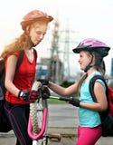 Die Mädchenkinder, die Familie radfahren, pumpen oben Fahrradreifen Stockbilder
