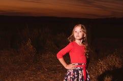 Die Mädchenkosten bei Sonnenuntergang Stockbild