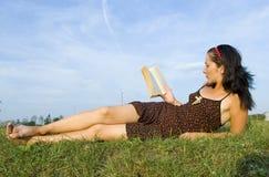 Die Mädchenlagen auf einem Gras Lizenzfreie Stockfotos