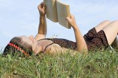 Die Mädchenlagen auf einem Gras Lizenzfreie Stockfotografie