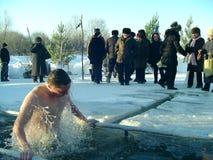 Die Männer badet in einem Eisloch auf dem Fluss Lizenzfreie Stockfotos