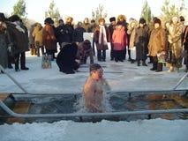 Die Männer badet in einem Eisloch auf dem Fluss Stockbilder