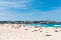 Die Männer, Frauen u. Kinder, die bei Bondi sich entspannen, setzen in Sydney, Australien auf den Strand Lizenzfreies Stockfoto