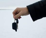 Die männliche Hand, die Autoschlüssel halten und das Warnungssystem bezaubern Stockbild