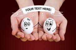 Die männliche Hand, die das Anhalten anhält, eggs mit smileygesichtern Lizenzfreie Stockfotos