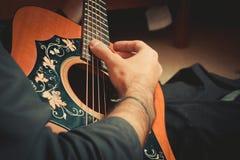 Die männliche Hand spielt die Schnüre der alten Gitarrennahaufnahme lizenzfreie stockfotos