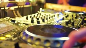 Die männliche Hand steuert die DJ-Konsole Der Raum wird mit gelbem Licht belichtet stock footage