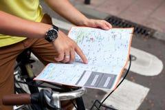 Die männlichen Hände, die auf die Karte von Barcelona-Stadt auf Retro- Fahrrad zeigen, fahren Hintergrund rad kleines blaues Auto stockbilder