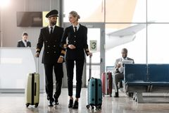 die männlichen und weiblichen Piloten, die durch Flughafen gehen, beeinflussen lizenzfreies stockfoto