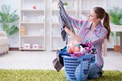 Die müde deprimierte Hausfrau, die Wäscherei tut Stockfoto