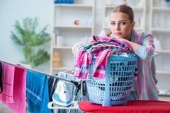 Die müde deprimierte Hausfrau, die Wäscherei tut Stockbild