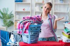 Die müde deprimierte Hausfrau, die Wäscherei tut Lizenzfreie Stockfotos