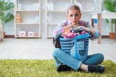 Die müde deprimierte Hausfrau, die Wäscherei tut Stockbilder