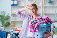 Die müde deprimierte Hausfrau, die Wäscherei tut Stockfotos
