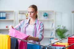 Die müde deprimierte Hausfrau, die Wäscherei tut Lizenzfreie Stockbilder