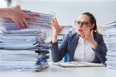 Die müde Geschäftsfrau mit Schreibarbeitsarbeitsbelastung Stockfoto