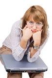 Die müde junge Frau sitzt mit dem Laptop Lizenzfreie Stockbilder