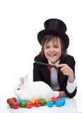 Die Magie von Ostern - glücklicher Magierjunge und mürrisches Kaninchen Lizenzfreies Stockfoto