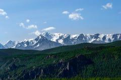 Die malerische Landschaft des Tales der Hügel bedeckt mit grünem Gras und Bäumen vor der Steinkante von Schnee-mit einer Kappe be stockfotografie