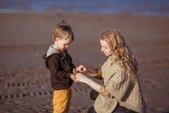 Die Mama hält die Hände ihres Sohns Stockfoto
