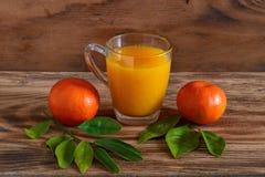 Die Mandarinen und der Tangerinesaft auf einem hölzernen Hintergrund Lizenzfreies Stockbild