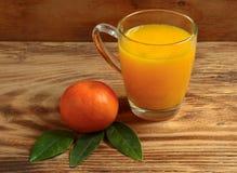 Die Mandarinen und der Tangerinesaft auf einem hölzernen Hintergrund Lizenzfreie Stockbilder