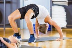 Die Mann-Ausführung biegen Haltung auf Mat In Gym zurück stockfoto