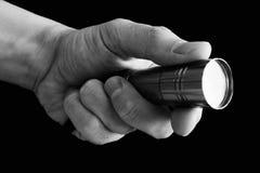 Die Mann ` s Hand, die eine Taschenlampe auf schwarzem Hintergrund hält Lizenzfreie Stockbilder