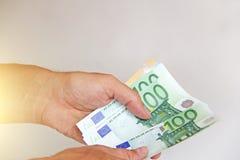 Die Mann ` s Hand hält den Euro 100, betrachtet sie und zahlt Papiergeldeuros in den Händen stockfotografie