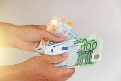 Die Mann ` s Hand hält den Euro 100, betrachtet sie und zahlt Papiergeldeuros in den Händen stockbild
