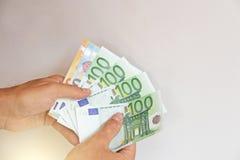 Die Mann ` s Hand hält den Euro 100, betrachtet sie und zahlt Papiergeldeuros in den Händen stockfoto