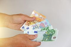 Die Mann ` s Hand hält den Euro 100, betrachtet sie und zahlt Papiergeldeuros in den Händen lizenzfreie stockfotografie