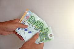 Die Mann ` s Hand hält den Euro 100, betrachtet sie und zahlt Papiergeldeuros in den Händen lizenzfreie stockfotos