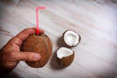 Die Mann ` s Hand hält eine Kokosnuss mit einem eingefügten Stroh Lizenzfreies Stockfoto