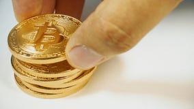 Die Mann ` s Hand setzt die bitcoins in eine Spalte ein Hand, die Gold-bitcoins zählt Schlüsselwährung Gold Bitcoin - BTC - Stück Lizenzfreie Stockbilder