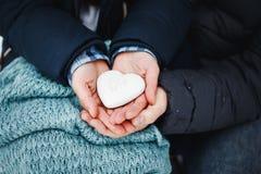 Die Mann- und Frauenhände, die Herz halten, formen Plätzchen Stockfotografie
