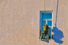 Die Mannarbeitskraft, die an der Baustelle mit Sturzhelm und an der Uniform für äußeres Gebäude der Arbeiten klettert stockbild