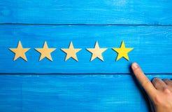 Die Manneshand zeigt auf den fünften gelben Stern auf einem blauen hölzernen Hintergrund Fünf Sterne Bewertung des Restaurants od lizenzfreie stockfotos