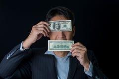 Die Mannhände, die Dollarbanknote halten, nahmen seinen Mund und Augen auf Stockbilder