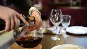Die Mannhand, die den Rotwein von der Flasche in das Dekantiergefäß gießt Lizenzfreie Stockfotos