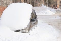 Die Maschine wird mit Schnee bedeckt Autogriff mit einem Stapel des Schnees Verschrottung von Maschinen nach Schneefällen lizenzfreie stockbilder