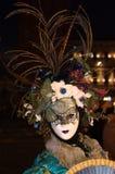 Die Maske mit dem Hut von Blumen und von Federn am Venedig-Karneval stockfotografie