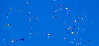 Die mehrfarbigen Bälle, gefüllt mit Helium, fliegen in den blauen Himmel stockbild