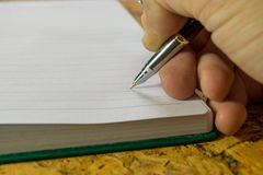 Die menschliche Hand mit Anmerkungen eines Stiftschreibens in einem Tagebuch Lizenzfreies Stockfoto